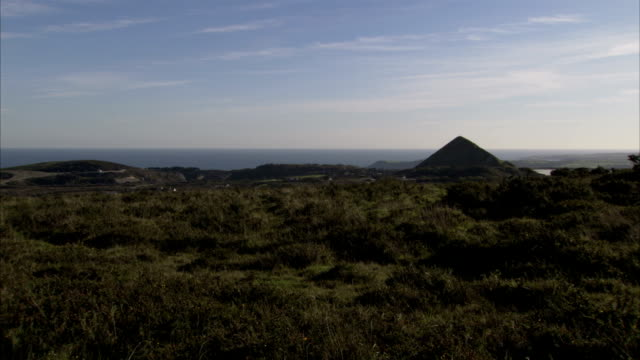 vídeos de stock e filmes b-roll de cornish countryside marked by a pyramid created by china clay quarrying and sea beyond. available in hd. - pyramid