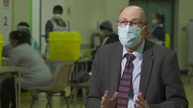 professor stephen powis interview; england: london: southall: int professor stephen powis interview sot (blurred shot of people being vaccinated in... - inch stock videos & royalty-free footage