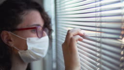 Corona covid-19 virus protection. Isolated sick woman with mask at hospital quarantine look through window blinds