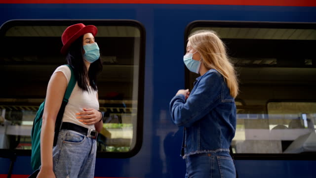 corona virus greeting. two young friends meeting on railroad station,ready for travel. - railway station platform stock videos & royalty-free footage