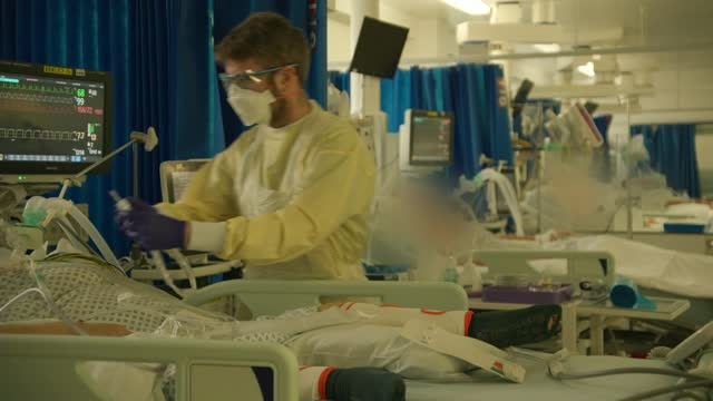 covid patients being treated at st george's hospital; england: london: tooting: st george's hospital: int medics working in acute dependency unit... - epidemic stock-videos und b-roll-filmmaterial