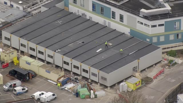aerials of london testing centres and temporary mortuaries; england: london: ext air view hillingdon hospital and construction workers on roof of... - major road video stock e b–roll