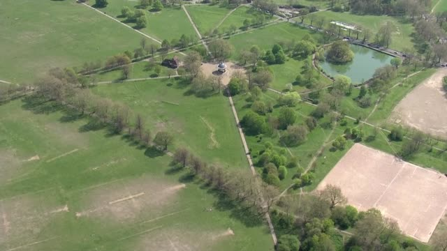 air views of london parks during lockdown; england: london: clapham common: ext air view wardens along through park / couple exercising with fitness... - battersea park stock videos & royalty-free footage