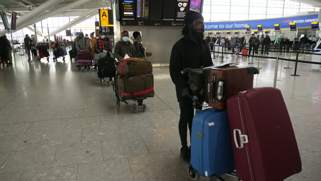 airport bosses warn government hotel quarantine policy is not ready ahead of launch; england: london: heathrow: int gvs people in masks with... - suitcase stock videos & royalty-free footage