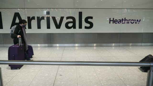 airport bosses warn government hotel quarantine policy is not ready ahead of launch; england: london: heathrow: int gvs international arrivals along... - suitcase stock videos & royalty-free footage