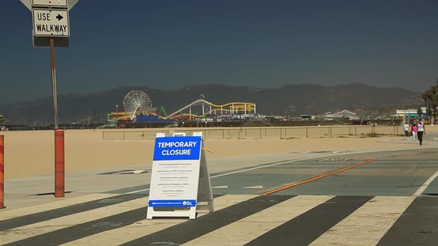 coronavirus and 4th of july weekend - cyclists and walkers in front of closed santa monica beach - santa monica pier sign stock videos & royalty-free footage
