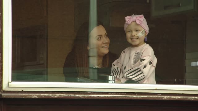 ant and dec 'stay at home' video message on behalf of four-year-old with cancer; scotland: falkirk: ext various of mila sneddon and her mother lynda... - window stock videos & royalty-free footage