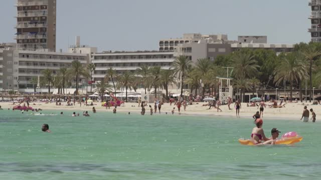 balearic islands to placed back on amber list; spain: balearic islands: ext various of holidaymakers on beach and in sea, hotels in background back... - spain stock videos & royalty-free footage