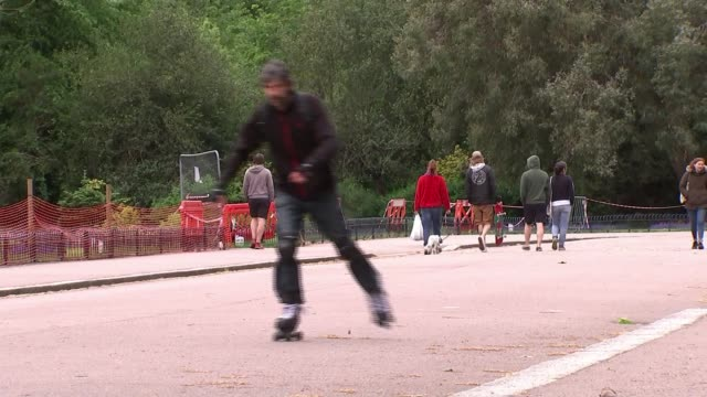 boris johnson outlines plans to relax lockdown; england: london: victoria park: ext gv man wearing roller skates along towards camera gv girls away... - itv weekend late news点の映像素材/bロール