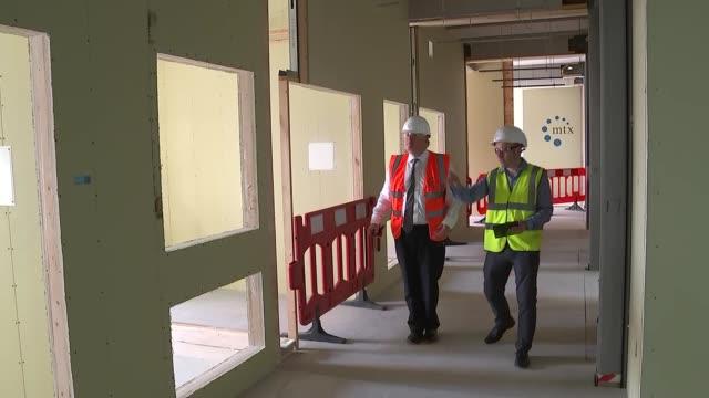 boris johnson visits construction site / interview; england: hertfordshire: int boris johnson mp smoothing plaster / boris johnson speaking about... - scrubs stock videos & royalty-free footage