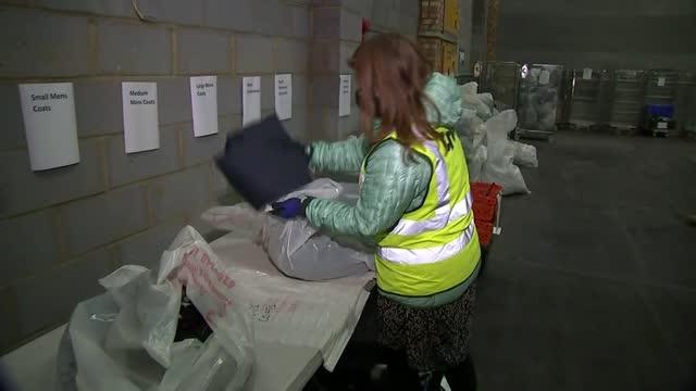 vídeos de stock e filmes b-roll de charities struggle to support homeless through winter during the pandemic; england: london: poplar: int various shots of volunteers putting donations... - desodorante