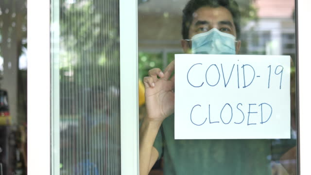 coronavirus closed for business concept, male with medical mask puts sorry closed sign on window due to covid 19. - terrified stock videos & royalty-free footage