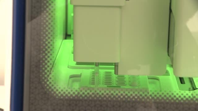 collinson biotech coronavirus testing laboratory; england: london: near heathow: collinson biotech laboratory: int scientist operating machine in... - biotechnology stock videos & royalty-free footage