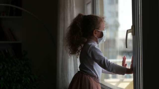 covid-19 coronavirus concept, little girl in face mask looking through window with note quarantine at home. sad kid during quarantine due to covid. - baby girls stock videos & royalty-free footage