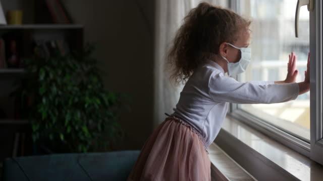 vídeos de stock, filmes e b-roll de conceito de coronavírus covid-19, menina com máscara facial olhando pela janela com nota quarentena em casa. criança triste durante a quarentena devido ao covid. - bebês meninas
