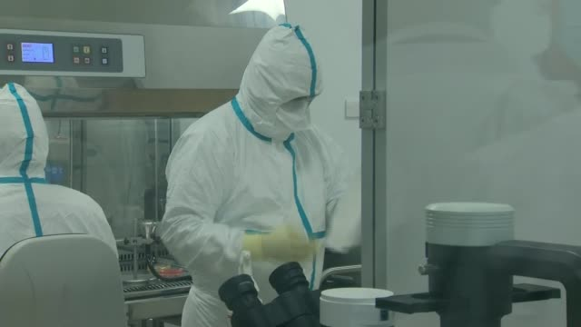 concern over numbers willing to take part in vaccine trial; scotland: livingston: int various shots of scientists/researchers, wearing full hazmat... - scientist stock videos & royalty-free footage