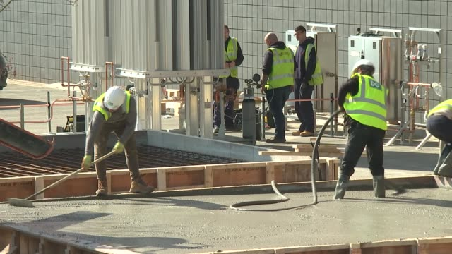 construction work at the excel centre/nhs nightingale hospital; england: east london: docklands: excel centre: ext workers laying concrete outside... - london docklands stock videos & royalty-free footage