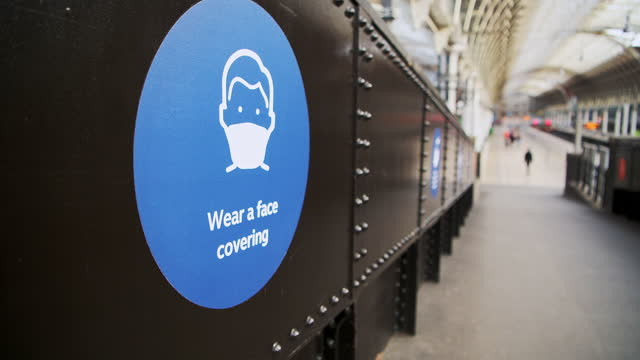 coronavirus covid-19 information sign saying wear a face covering mask at paddington train station in london when public transport was quiet and deserted with no people in england, europe - paddington railway station stock videos & royalty-free footage