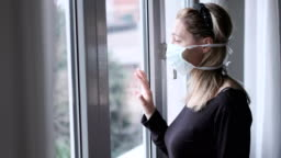 coronavirus covid-19 isolation - shaky camera scene of italian woman at window with a mask quarantine measures during virus outbreak
