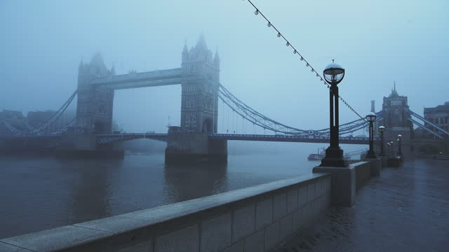 coronavirus covid-19 lockdown day one in foggy weather conditions at tower bridge in london, with quiet empty and deserted streets on a misty cool blue atmospheric morning in fog and mist , england, uk - fog stock videos & royalty-free footage