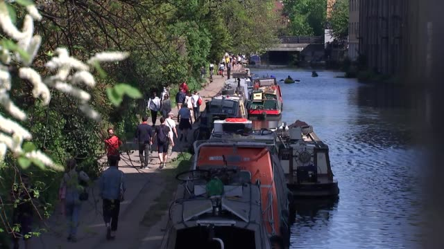 crowded canal towpath england london ext high angle view people along busy canal path and canal boats moored in foreground gv people along canal... - canal stock videos & royalty-free footage