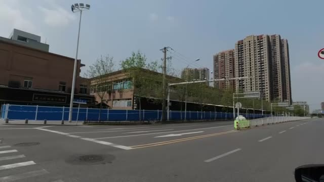 early survivor says it is unfair to blame outbreak on wuhan market; china: hubei province: wuhan: ext tracking shots empty road / barricades by wet... - boundary stock-videos und b-roll-filmmaterial