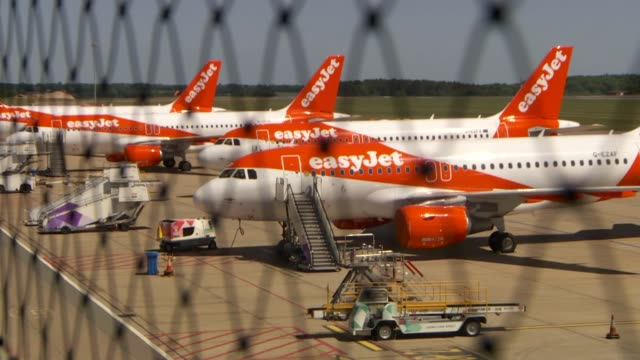 easyjet to cut flights, routes and up to 30 per cent of its staff; england: hertfordshire: luton airport: ext various shots of easyjet aircraft... - luton airport stock videos & royalty-free footage
