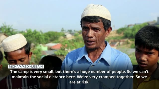 first coronavirus cases appear in rohingya refugee camps in bangladesh bangladesh cox's bazar ext pan refugees passing as carrying water in various... - rohingya kultur stock-videos und b-roll-filmmaterial