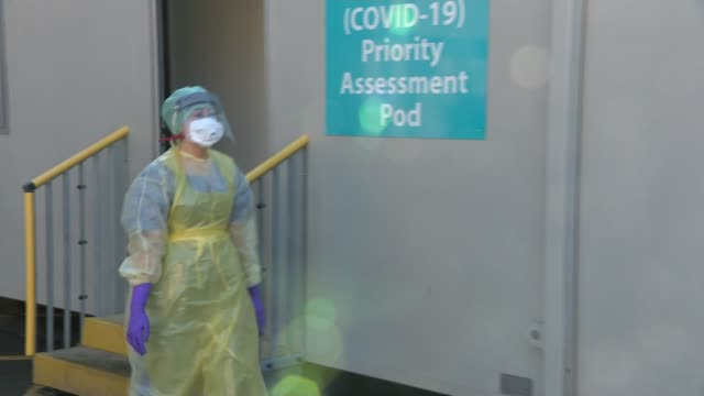 first uk death as country moves towards 'delay phase'; northern ireland: county antrim: ext gv masked medical worker outside 'coronavirus - covid 19... - ulster county stock videos & royalty-free footage