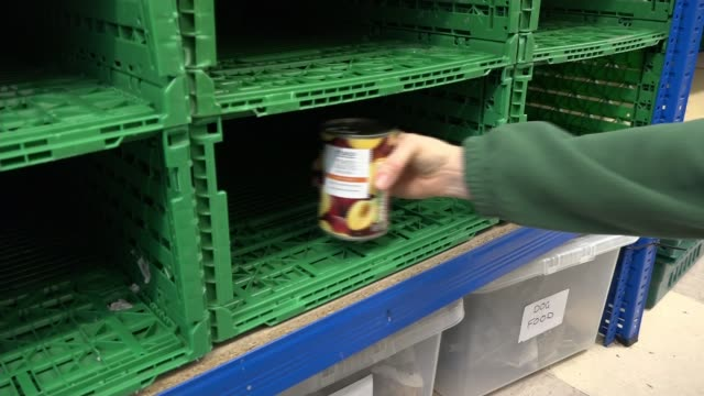food banks in london make a desperate plea for donations; england: london: hackney foodbank: int various of people dropping off food ext man pushing... - juice drink stock videos & royalty-free footage