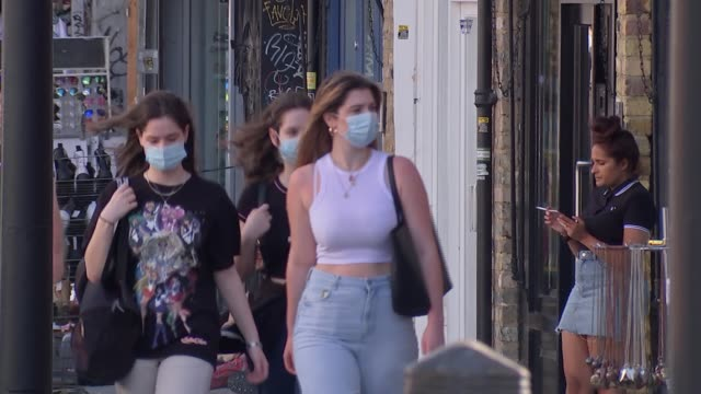 general views of people wearing masks in camden; england: london: camden: ext gvs people along past shops and market stalls, some wearing face masks... - general view stock videos & royalty-free footage
