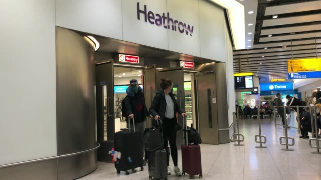 government puts in place further restrictions to try to curb spread of the disease; england: london: heathrow airport: int man and woman along in... - flughafen heathrow stock-videos und b-roll-filmmaterial