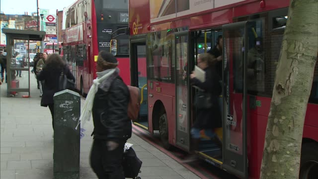 gvs of camberwell streets and crowds; england: london: camberwell: ext gvs people along street / gvs london buses / crowds along crossing street / - bus stock videos & royalty-free footage