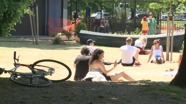gvs southbank centre / people enjoying sunshine in victoria park england london tower hamlets victoria park ext pond / gvs sunbathers / - pond stock videos & royalty-free footage
