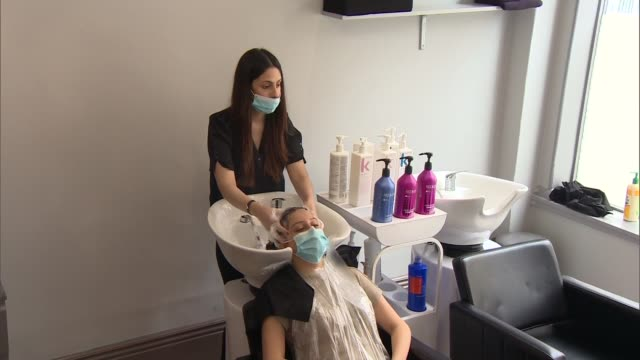 hair salon reopens; england: yorkshire: york: int various of hairdressers cutting and dying hair of customers in hair salon, all wearing face masks /... - hairstyle stock videos & royalty-free footage