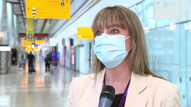 heathrow airport acquires new covid-cleaning robot; england: london: heathrow airport: reporter to camera person wearing mask along through airport... - bud stock videos & royalty-free footage