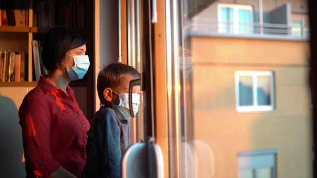 covid-19 - coronavirus - home quarantine - mother and son wearing masks looking trough the window - stay at home order stock videos & royalty-free footage
