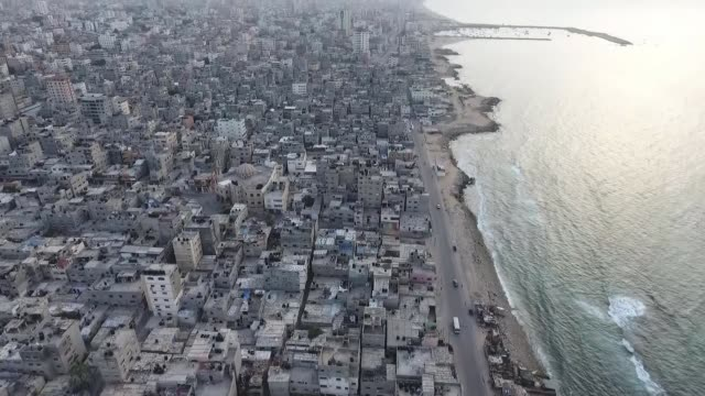 stockvideo's en b-roll-footage met hostility between israel and palestine decreasing in face of virus; palestine: gaza: ext air view drone shots of gaza city. - nederzettingen