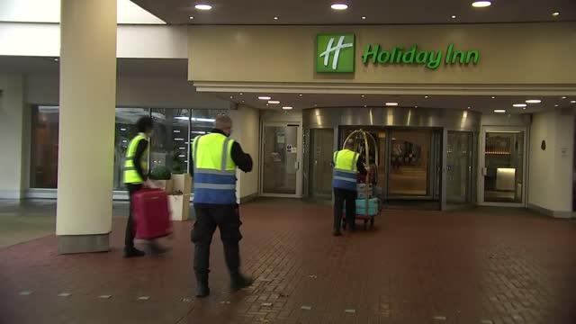 hotel quarantine begins as first guests check in for 10-day stay; england: london: heathrow: ext two airline passengers from coach at holiday inn... - hotel stock videos & royalty-free footage