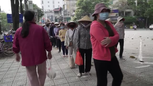 how vietnam contained coronavirus; vietnam: ext gv people wearing face masks queuing left and right rear view queues of people people queuing for... - vietnam stock videos & royalty-free footage