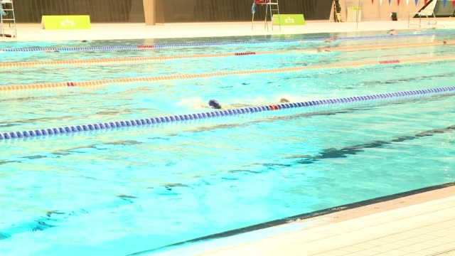 indoor swimming pools and gyms reopen in england today; england: london: stratford: london aquatics centre: int people swimming in lanes in pool... - lifeguard chair stock videos & royalty-free footage