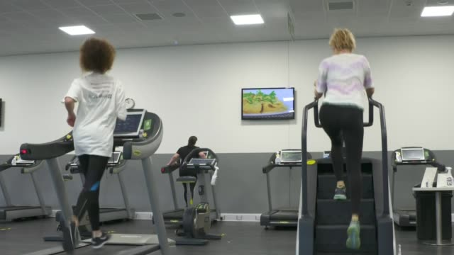 indoor swimming pools and gyms reopen in england today england london kensington leisure centre int man excising with weights in gym woman doing yoga... - exercise equipment stock videos & royalty-free footage
