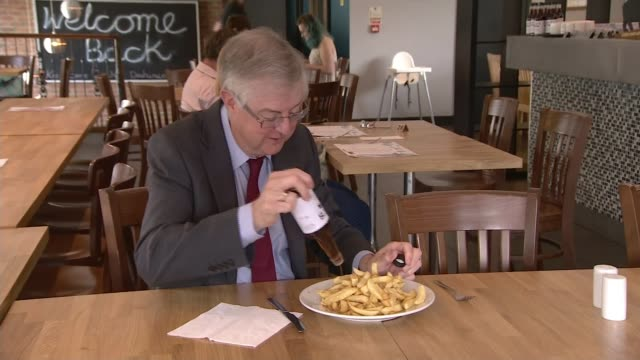 indoors restaurants and pubs reopen in wales wales int 'welcome back' sign / various of mark drakeford am eating plate of chips and chatting with... - plate stock videos & royalty-free footage