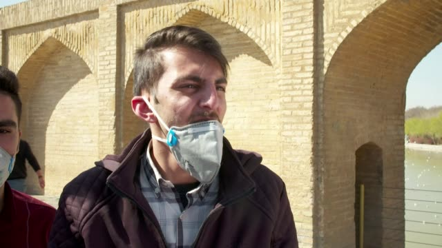 iran closes borders over virus fears during election iran isfahan gvs of bridge river architecture market square people wearing face masks horse and... - 宗教施設点の映像素材/bロール