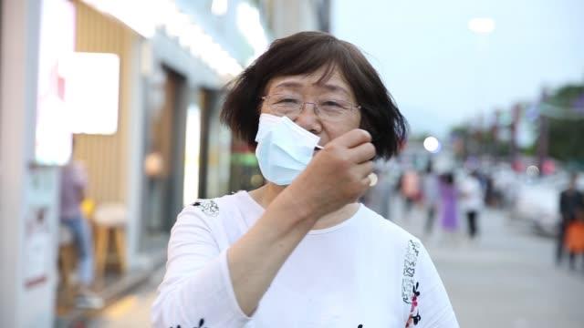 vídeos de stock e filmes b-roll de coronavirus is over!senior asian woman take off protective mask - remover