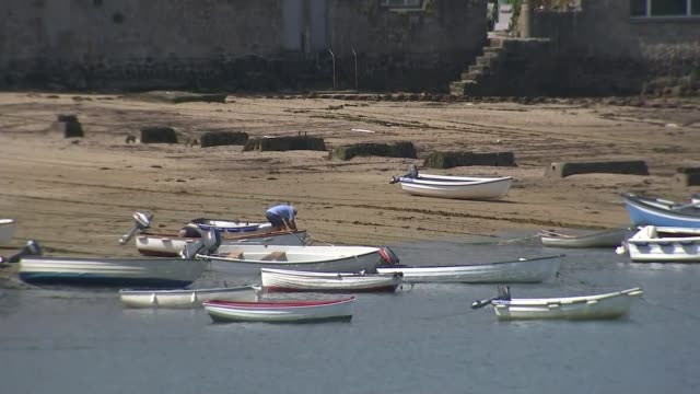 isles of scilly preparing to welcome back tourists; england: cornwall: isles of scilly: st mary's: hugh town: ext air views drone above ocean, beach,... - isles of scilly stock videos & royalty-free footage