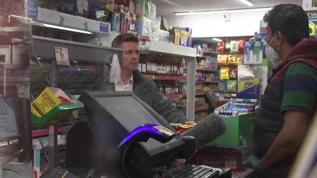 local corner shops become community lifelines in lockdown; england: ext low angle view shop shutters rising side view customers waiting for shop to... - snack stock videos & royalty-free footage