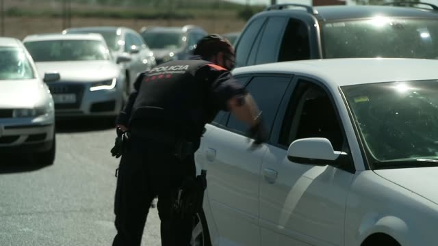 local lockdown enforced in catalonia spain catalonia ext various shots of cars being held at police check point - politics stock-videos und b-roll-filmmaterial