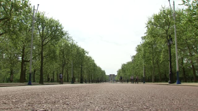 lockdown: the mall:; england: london: the mall: ext wide shot the mall and cyclists along left and right and police van parked on grass left and... - b rolle stock-videos und b-roll-filmmaterial