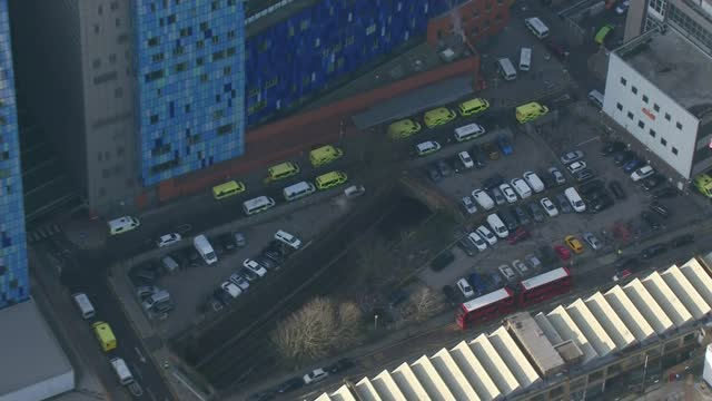 vídeos de stock, filmes e b-roll de london hospitals struggling to cope with influx of covid cases; england: london: romford: queen's hospital: ext air view ambulances waiting outside... - ilford